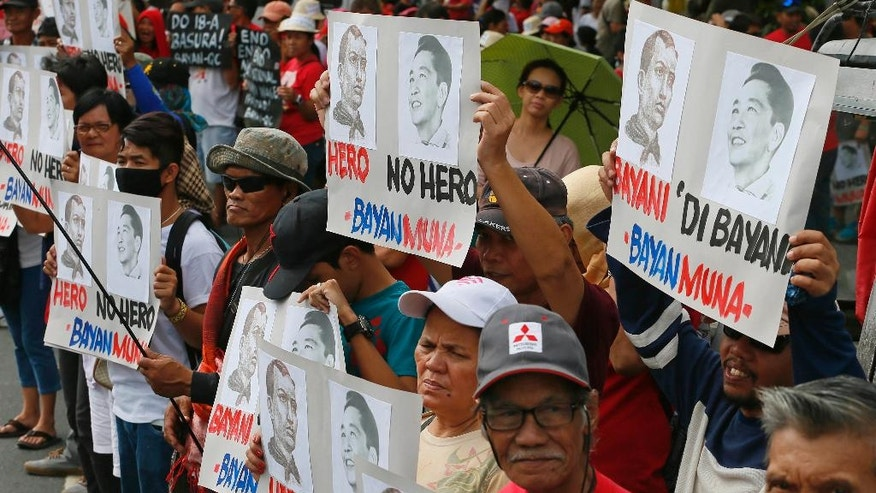 "Protesters display a combo portrait of the country's revolutionary hero Andres Bonifacio and the late dictator Ferdinand Marcos labeling him as ""No Hero"" prior to marching towards the Presidential Palace to protest Marcos' Nov. 18, 2016 burial at the Heroes' Cemetery Wednesday, Nov. 30, 2016 in Manila, Philippines. Protests are mounting since the hasty burial of the long-dead Marcos in a heroes' cemetery, in a growing political storm that's lashing the president who allowed the entombment. (AP Photo/Bullit Marquez)"