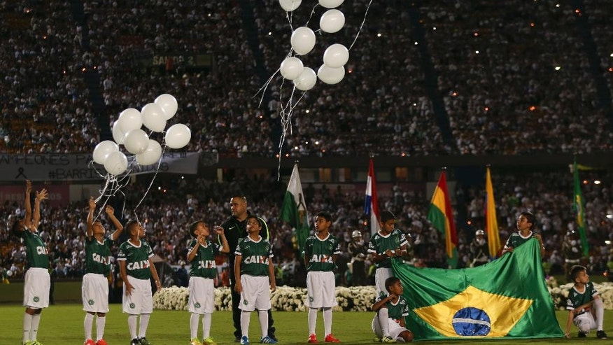 Children release balloons during a tribute to members of Brazil's Chapecoense soccer team who died in a plane crash, at Atanasio Girardot stadium where they were to play a game in Medellin, Colombia, Wednesday, Nov. 30, 2016. Brazil's team was traveling to Colombia to meet up with Atletico Nacional on Wednesday night for the Copa Sudamericana final. (AP Photo/Fernando Vergara)