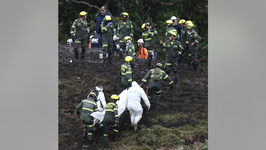 Rescue workers remove the body of a victim of an airplane crash in La Union, near Medellin, Colombia, Tuesday, Nov. 29, 2016. The plane was carrying the Brazilian first division soccer club Chapecoense team that was on it's way for a Copa Sudamericana final match against Colombia's Atletico Nacional. (AP Photo/Fernando Vergara)