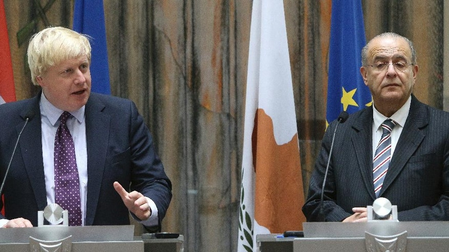 """Britain's foreign secretary Boris Johnson, left, and his Cypriot counterpart Ioannis Kasoulides speak to the media after their meeting at the foreign house, in Nicosia, Cyprus, on Wednesday, Nov. 30, 2016. Britain's foreign secretary says the U.K.'s support for Cyprus amid talks aimed at reunifying the ethnically split island remains """"rock solid."""" Johnson is in Cyprus for three-days official visit. (AP Photo/Petros Karadjias)"""