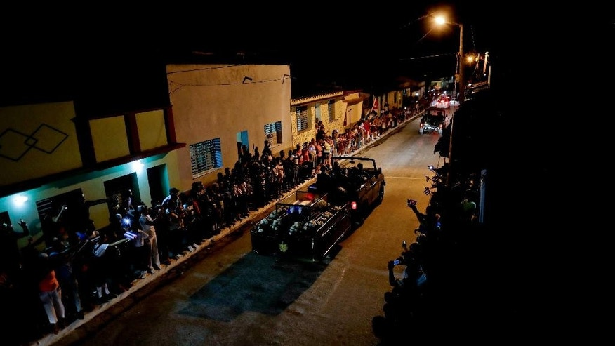 People gather in the street to watch Fidel Castro's funeral procession, as his ashes pass through Esperanza, Cuba, Wednesday, Nov. 30, 2016. Castro's ashes have begun a four-day journey, retracing the path of his triumphant march into Havana nearly six decades ago, to their final resting place in the eastern city of Santiago. (AP Photo/Natacha Pisarenko)