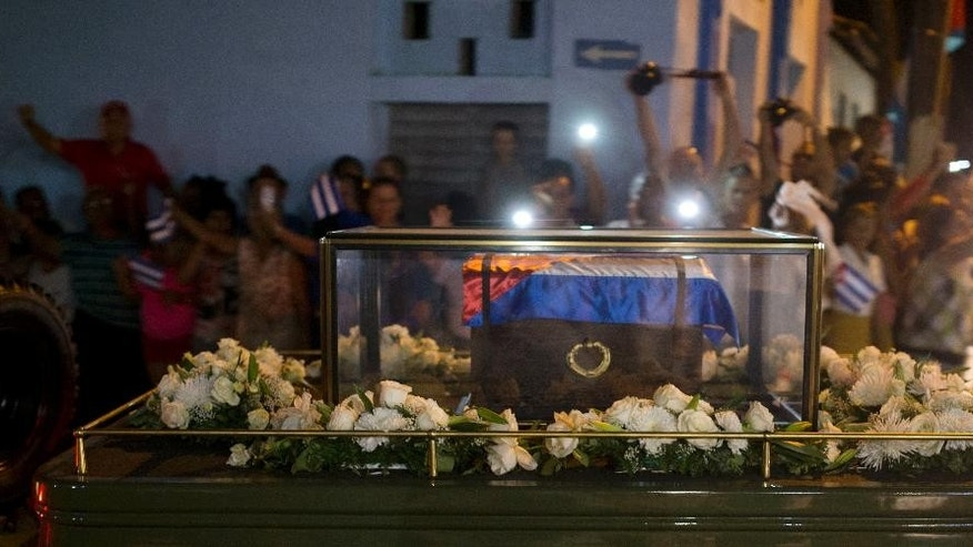 A small coffin covered by a Cuban flag with the ashes of the late Fidel Castro are carried on a trailer during a funeral procession that retraces the path of Castro's triumphant march into Havana nearly six decades ago, in La Esperanza, Cuba, Wednesday, Nov. 30, 2016. Castro's ashes have begun a four-day journey across Cuba from Havana to their final resting place in the eastern city of Santiago. (AP Photo/Ricardo Mazalan)
