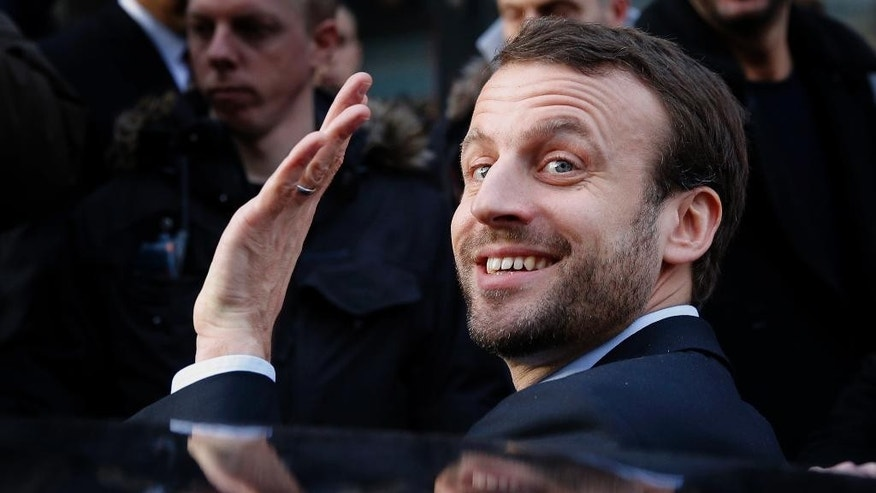 FILE - In this Jan.6, 2016 file photo, French Economy Minister Emmanuel Macron waves as he leaves after a visit to a shopping center in Paris, France. France's presidential candidate Emmanuel Macron pledges for re-opening discussions with Russia and make from the fight against the Islamic State group a priority. (AP Photo/Christophe Ena, File)