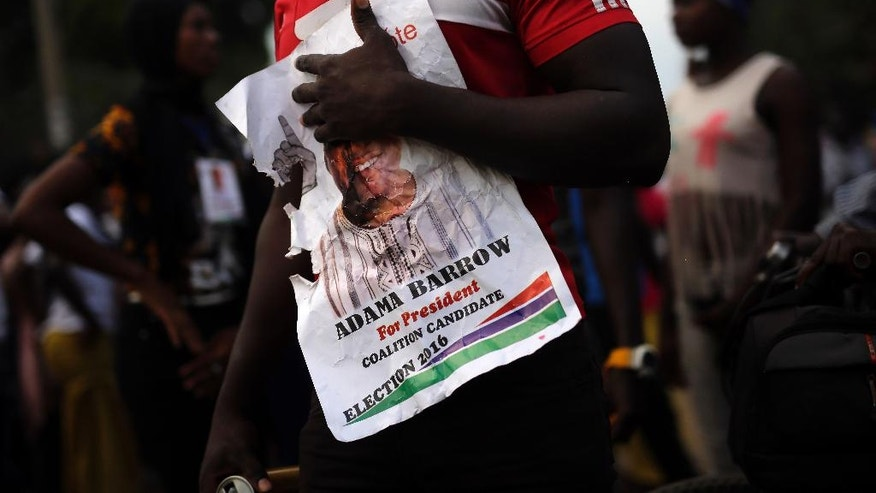 """Opposition coalition candidate Adama Barrow's supporter holds a poster of his candidate in the """"Buffer Zone"""" district of Talinding in the outskirts of Banjul, Gambia, Tuesday Nov. 29, 2016. Gambia's opposition parties are rallying together behind a single candidate for the first time in decades, forming a coalition they hope will oust longtime President Yahya Jammeh, who has been accused of human rights abuses throughout his 22-year rule. (AP Photo/Jerome Delay)"""