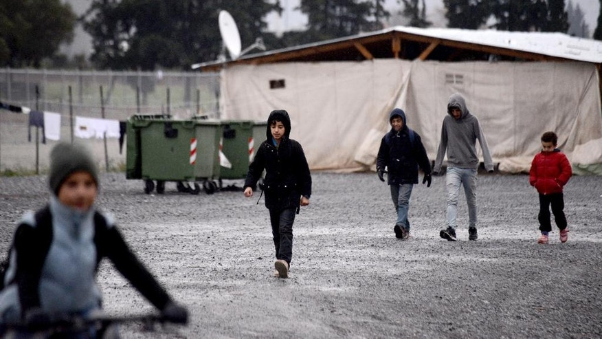 Children walk inside a refugee camp, in the village of Vasilika near the northern Greek city of Thessaloniki, on Tuesday, Nov. 29, 2016. Temperatures in northern Greece are set to plunge below zero overnight Tuesday for the first time in the region this winter, finding thousands of immigrants still stranded in tents at refugee camps in area. (AP Photo/Giannis Papanikos)