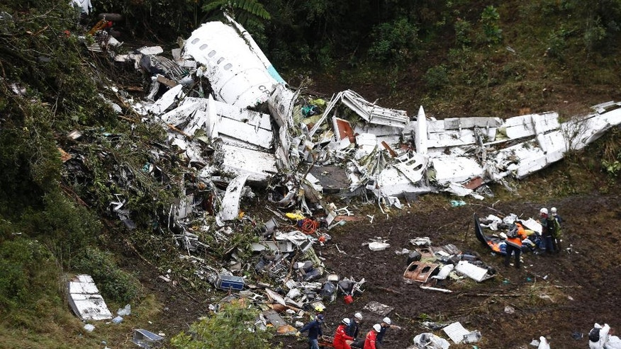 Rescue workers recover a body from the wreckage site of an airplane crash, in La Union, a mountainous area near Medellin, Colombia, Tuesday, Nov. 29, 2016. The plane was carrying the Brazilian first division soccer club Chapecoense team that was on it's way for a Copa Sudamericana final match against Colombia's Atletico Nacional. (AP Photo/Fernando Vergara)