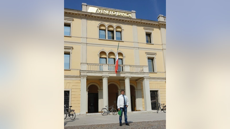 This Sept. 28, 2016 photo shows Investor Walter Baseggio posing in front of the historic headquarters of Veneto Banca, in Montebelluna, near Treviso, Italy. Veneto Banca was an integral part of the community before it collapsed, causing losses for thousands of savers, many of them elderly, its demise is emblematic of the wider country's financial problems, which could get worse if the government collapses after a popular vote this weekend on Dec. 4, 2016. (AP Photo/Colleen Barry)