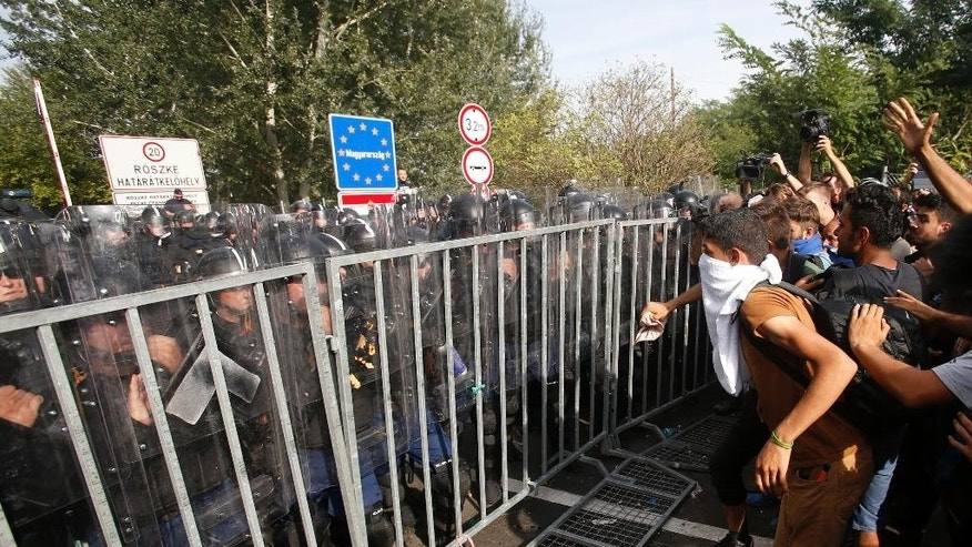 "FILE- In this Sept. 16, 2016 file picture migrants protest at the ""Horgos 2"" border crossing into  Hungary, near Horgos, Serbia. A Hungarian court  Wednesday Nov. 30, 2016 has sentenced a Syrian man to 10 years in prison for taking part in a Sept. 2015 riot after Hungary closed its borders to migrants and refugees.Dozens of police officers, migrants and some journalists were injured in clashes on Sept. 16, 2015, a day after Hungary closed off its border with Serbia with a fence protected by razor wire, stranding hundreds of migrants.  (AP Photo/Darko Vojinovic,file)"