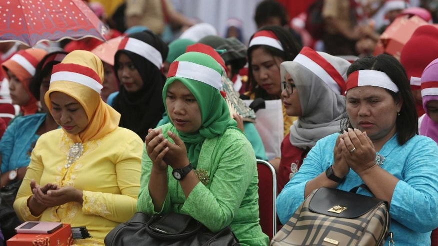 Locals pray during a military-sponsored interfaith rally held ahead of the planned Dec. 2 Muslim protest against Jakarta Governor Basuki Tjahaja Purnama in Jakarta, Indonesia, Wednesday, Nov. 30, 2016. Thousands of Indonesians have joined interfaith rallies around the country organized by the military in an attempt to demonstrate national unity as religious and racial tensions divide the world's largest Muslim nation. (AP Photo/Achmad Ibrahim)