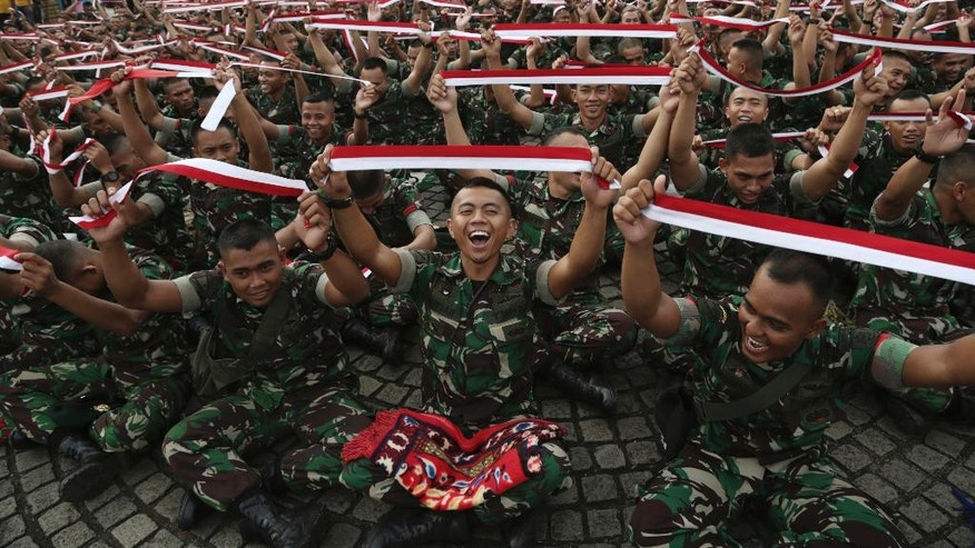 Indonesian soldiers hold up headbands in the color of the national flag during a military-sponsored interfaith rally held ahead of the planned Dec. 2, Muslim protest against Jakarta Governor Basuki Tjahaja Purnama in Jakarta, Indonesia, Wednesday, Nov. 30, 2016. Thousands of Indonesians have joined interfaith rallies around the country organized by the military in an attempt to  demonstrate national unity as religious and racial tensions divide the world's largest Muslim nation. (AP Photo/Achmad Ibrahim)