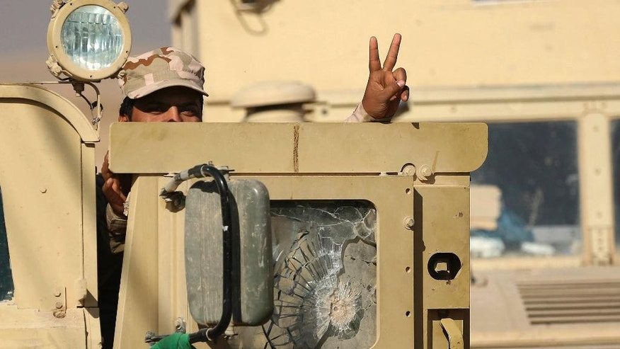 An Iraqi Army soldier flashes a victory sign as he leaves his armored vehicle after a military operation to regain control of a village outside Mosul, Iraq, Tuesday, Nov. 29, 2016. Iraqi forces are assaulting villages far south of Mosul in the Nineveh province, attempting to clear rural areas of Islamic State fighters who stayed behind to hinder their advance. (AP Photo/Hadi Mizban)