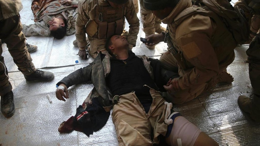 Iraqi injured soldiers, who were wounded during the battle against the Islamic State group, lies on the ground as they receive medical treatment at a field hospital, in Haj Ali frontline village, southern Mosul, Iraq, Tuesday, Nov. 29, 2016. Iraqi forces on Tuesday assaulted villages far south of Mosul in the Nineveh province, attempting to clear rural areas of Islamic State fighters who stayed behind to hinder their advance. (AP Photo/Hussein Malla)