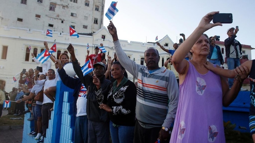People wave Cuban national flags as they watch the motorcade transporting the remains of Cuban leader Fidel Castro drive past, along the Malecon seaside boulevard, in Havana, Cuba, Wednesday, Nov. 30, 2016. Castro's ashes have begun a four-day journey across Cuba from Havana to their final resting place in the eastern city of Santiago.  (AP Photo/Dario Lopez-Mills)