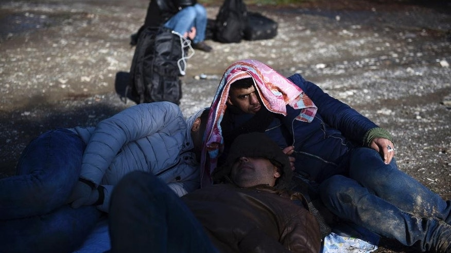 Syrian refugees wait to be picked up by the police on the outskirts of the northern Greek city of Thessaloniki, on Wednesday, Nov. 30, 2016. Authorities in Greece say they have picked up about 70 migrants, including children, found in the forested area after a truck driver left them and they spent the night there in the snow. (AP Photo/Giannis Papanikos)