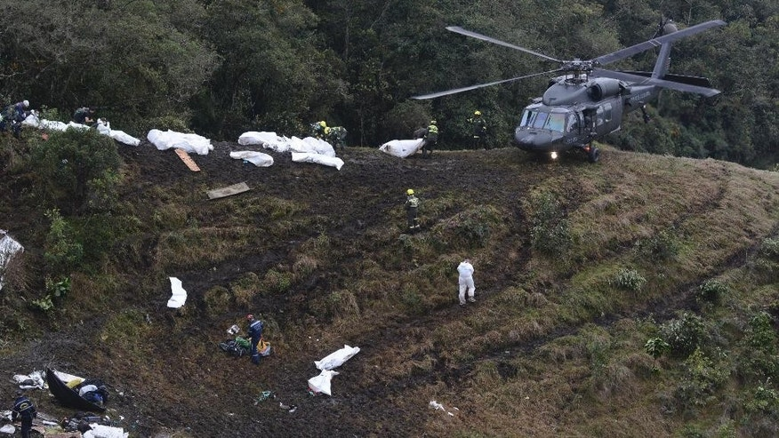 Rescue workers place the bodies of victims of an airplane crash into a waiting helicopter, in La Union, near Medellin, Colombia, Tuesday, Nov. 29, 2016. The chartered plane was carrying a Brazilian soccer team to the biggest match of its history when it crashed into a Colombian hillside and broke into pieces, Colombian officials said Tuesday. (AP Photo/Luis Benavides)