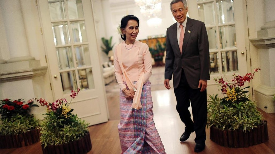 Myanmar's Foreign Minister Aung San Suu Kyi, left, steps into a photo position for the media along with Singapore's Prime Minister Lee Hsien Loong at the Istana or presidential palace on Wednesday, Nov. 30, 2016, in Singapore. Suu Kyi is on a three day official visit to the city-state. (AP Photo/Wong Maye-E)