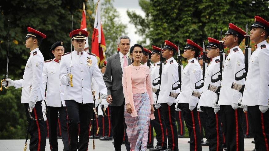 Myanmar's Foreign Minister Aung San Suu Kyi, center front, is accompanied by Singapore's Prime Minister Lee Hsien Loong as she inspects honor guards during a welcome ceremony at the Istana or presidential palace on Wednesday, Nov. 30, 2016, in Singapore. Suu Kyi is on a three day official visit to the city-state. (AP Photo/Wong Maye-E)
