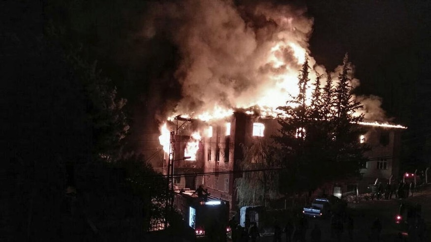 Flames rise from a fire in a school dormitory, in Aladag, Adana in southern Turkey, Tuesday, Nov. 29, 2016. A fire at a middle school dormitory for girls in southern Turkey has left over ten people dead and over a dozen injured, a Turkish governor and state-run media said. (DHA via AP)