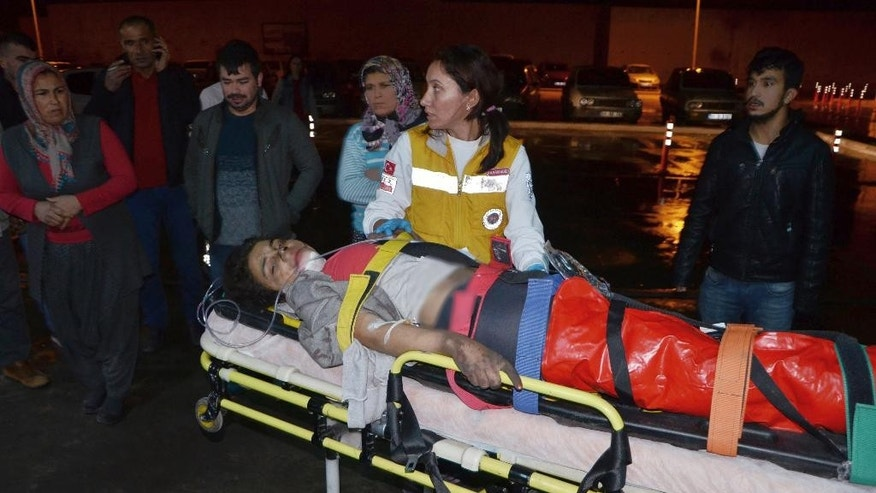 Medics carry a wounded student to an ambulance in Aladag, Adana in southern Turkey, late Tuesday, Nov. 29, 2016.  A fire at a middle school dormitory for girls in southern Turkey has left over ten people dead and over a dozen injured, a Turkish governor and state-run media said. (IHA via AP)
