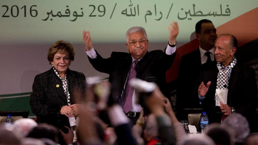 "Palestinian President Mahmoud Abbas, center, is greeted by fellow Fatah members as he arrives during the second day of the Fatah party conference, in the West Bank city of Ramallah, Wednesday, Nov. 30, 2016. Palestinian Fatah movement holds its seventh conference in Ramallah with some fourteen hundred members participating and led by Palestinian President Mahmoud Abbas. The conference is to elect the party's two main decision making bodies. Arabic reads "" Palestine, Ramallah, November 29, 2016."" (AP Photo/Majdi Mohammed)"
