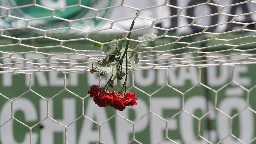 Flowers hang from a soccer net at the Arena Conda stadium in Chapeco, Brazil, Tuesday, Nov. 29, 2016. A chartered plane that was carrying the Brazilian soccer team Chapecoense to the biggest match of its history crashed into a Colombian hillside and broke into pieces, Colombian officials said Tuesday. (AP Photo/Andre Penner)