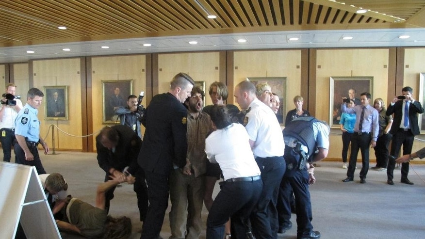 Security officers remove protesters from Parliament House in Canberra, Australia, on Wednesday, Nov. 30, 2016. Rowdy protesters demonstrating against Australia's treatment of asylum seekers have caused a brief disruption in Parliament, with security officers finally wresting them out. (AP Photo/Rod McGuirk)