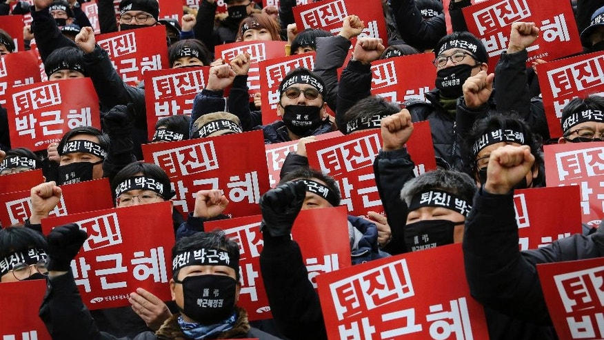 """Protesters shout slogans during a rally calling for South Korean President Park Geun-hye to step down in Seoul, South Korea, Wednesday, Nov. 30, 2016. South Korea's three main opposition parties agreed Wednesday to stick to their plans to impeach Park, dismissing as a stalling tactic her offer to resign if parliament arranges a safe transfer of power. The letters read """"Park Geun-hye to step down"""". (AP Photo/Ahn Young-joon)."""