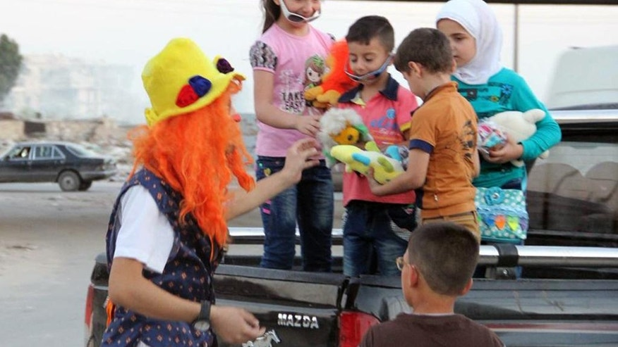 This undated photo courtesy of Ahmad al-Khatib, a media activist in Aleppo, shows Syrian social worker Anas al-Basha, 24, dressed as a clown, distributing toys to children in Aleppo, Syria. Al-Basha, was a center director at Space for Hope, one of the many important but unheralded local initiatives that has operated against the odds to provide the services of civil society in Syria's war-torn opposition areas. He was killed on Tuesday, Nov. 29, 2016 in a presumed government or Russian ballistic missile strike on the Mashhad neighborhood in the besieged, eastern side of Aleppo city. (Courtesy of Ahmad al-Khatib, via AP)