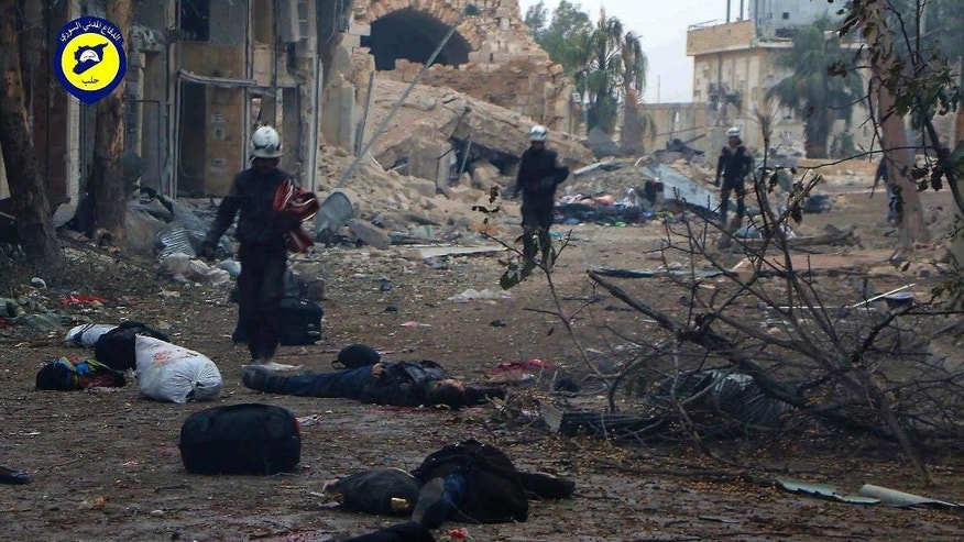 This photo provided by the Syrian Civil Defense White Helmets, which has been authenticated based on its contents and other AP reporting, shows Civil Defense workers pass by bodies after artillery fire struck the Jub al-Quba district in Aleppo, Syria, Wednesday, Nov. 30, 2016. Syrian activists say at least 21 people have been killed in an artillery barrage on a housing area for those displaced in rebel-held eastern Aleppo. (Syrian Civil Defense White Helmets via AP)