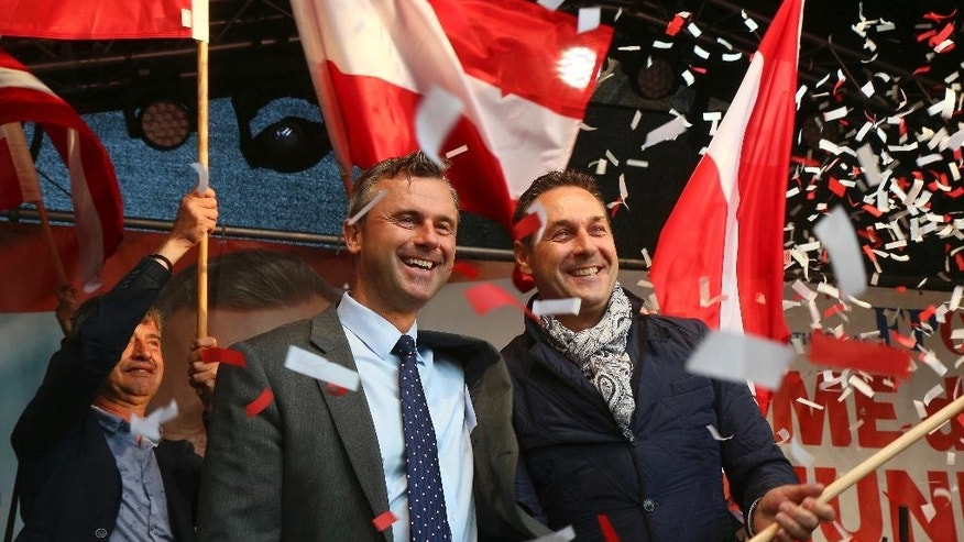 FILE - In this May 20, 2016 file photo Norbert Hofer candidate for presidential elections of Austria's Freedom Party, FPOE, and Heinz-Christian Strache, from left, head of Austria's Freedom Party, FPOE, look out at supporters during the final election campaign event in Vienna.  Austrians are choosing Sunday, Dec. 4, 2016 between a moderate and a populist for president _ and both candidates are hoping to exploit the Trump effect in the first European Union nation facing such a choice since the U.S election. (AP Photo/Ronald Zak, file)