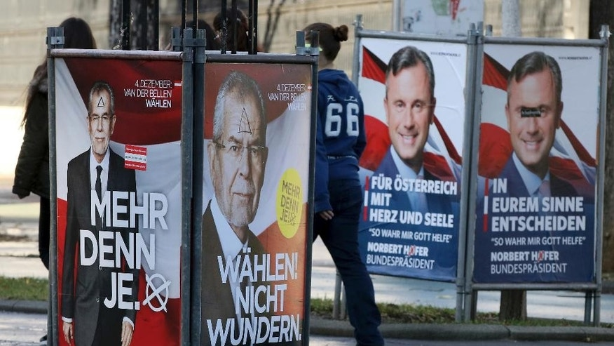 FILE - In this Nov. 22, 2016 photo people walk between election posters of Alexander Van der Bellen, candidate for presidential elections and former head of the Austrian Greens, and Norbert Hofer, from left, candidate for presidential elections of Austria's right-wing Freedom Party, FPOE, in Vienna, Austria. Austrians are choosing Sunday, Dec. 4, 2016 between a moderate and a populist for president _ and both candidates are hoping to exploit the Trump effect in the first European Union nation facing such a choice since the U.S election.  (AP Photo/Ronald Zak)