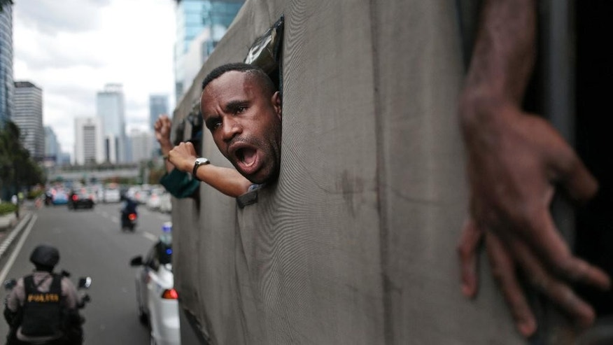 A West Papuan protester shouts slogans as he and others are taken away on a police truck during a rally calling for the remote region's independence, in Jakarta, Indonesia, Thursday, Dec. 1, 2016. Dozens of demonstrators were blocked from marching onto a busy traffic circle in the capital by several hundred police who fired water cannons and dragged men from the crowd into waiting police vans. (AP Photo/Dita Alangkara)