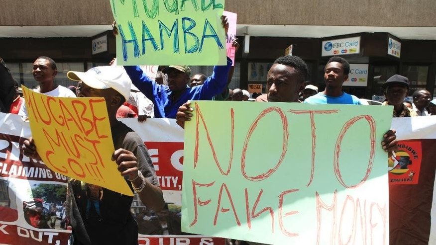 A group of protestors carry placards while demonstrating against the introduction of bond notes in Harare, Wednesday, Nov, 30, 2016. Zimbabwe Riot police fired teargas to disperse scores of activists protesting against the introduction of a new currency in the capital Harare. (AP Photo/Tsvangirayi Mukwazhi)