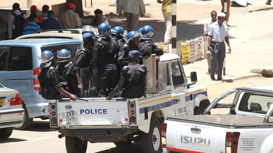 A police vehicle carrying riot police on patrol following demonstrations against bond notes in Harare, Wednesday, Nov, 30, 2016. Zimbabwe Riot police fired teargas to disperse scores of activists protesting against the introduction of a new currency in the capital Harare. (AP Photo/Tsvangirayi Mukwazhi)