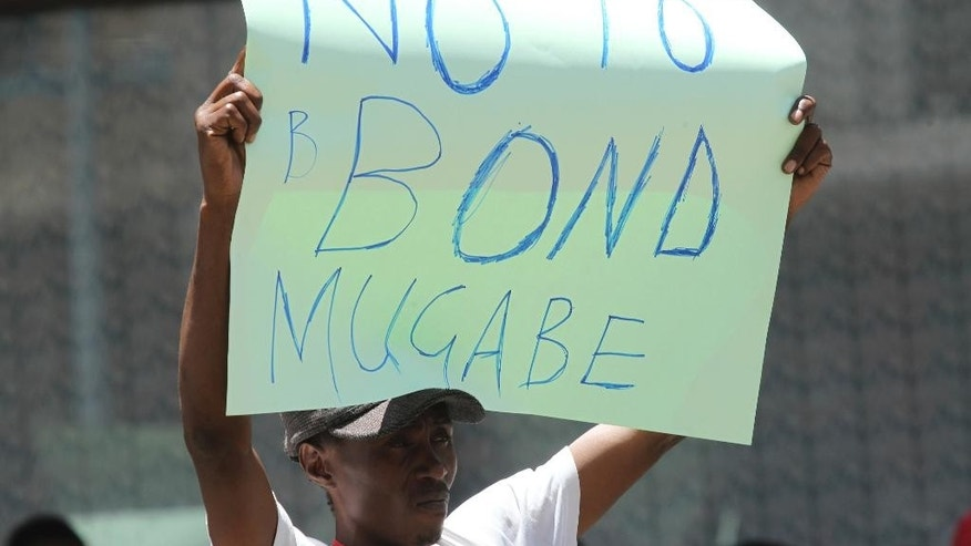 A protestor carries a placard while demonstrating against the introduction of bond notes in Harare, Wednesday, Nov, 30, 2016. Zimbabwe riot police fired teargas to disperse scores of activists protesting against the introduction of a new currency in the capital Harare. (AP Photo/Tsvangirayi Mukwazhi)