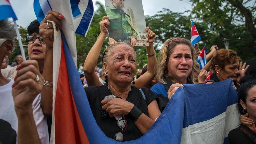 Women weep as the procession carrying the ashes of Cuba's leader Fidel Castro leaves the town of Santa Clara, Cuba, Thursday, Dec. 1, 2016. Castro's ashes are in a four-day journey across Cuba from Havana to their final resting place in the eastern city of Santiago. (AP Photo/Desmond Boylan)