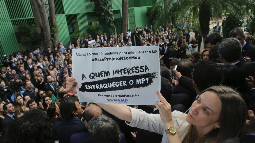 "A prosecutor holds a sign that says in Portuguese ""Who cares about the public prosecutor?"" to protest lawmakers' attempt to pass legislation that would allow judges and prosecutors to be charged with abuse of authority, in Brasilia, Brazil, Thursday, Dec. 1, 2016. Brazilian prosecutors are threatening to quit their investigation into a corruption-kickback scheme at state oil company Petrobras if the legislation is signed by President Michel Temer. (AP Photo/Eraldo Peres)"