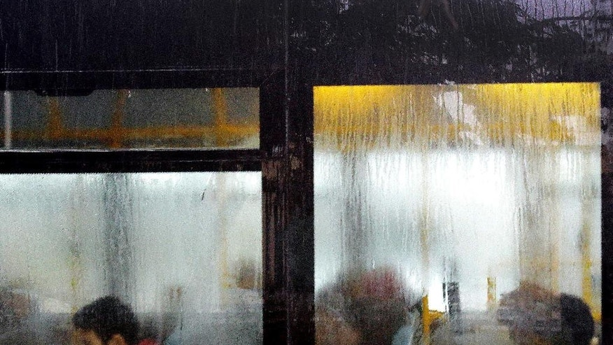Passenger are seen through the windows of a bus during heavy rain in the Turkish Cypriot breakaway northern part of the divided capital Nicosia in Cyprus, Thursday, Dec. 1, 2016. (AP Photo/Petros Karadjias)