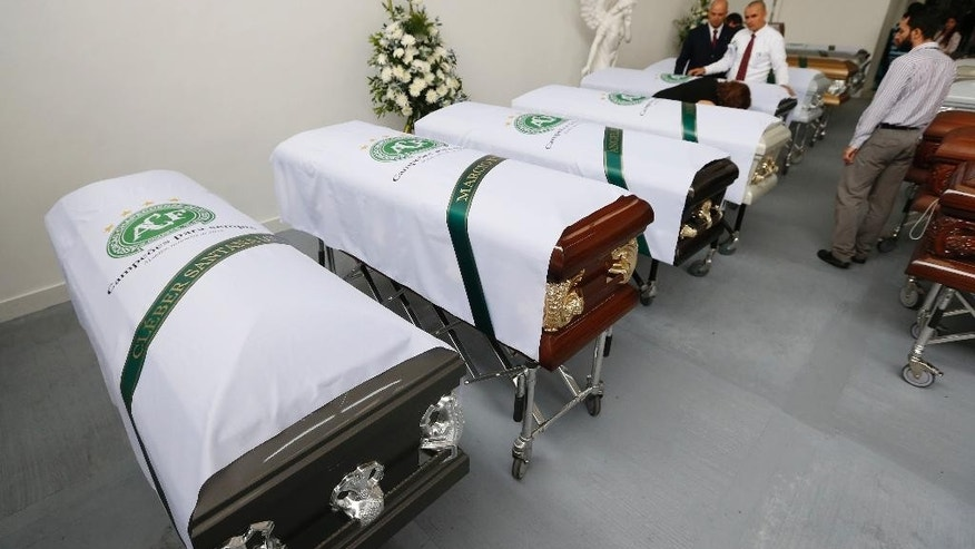 Funeral employees place white sheets with a Chapecoense soccer team logo on caskets containing the remains of team members, in Medellin, Colombia, Thursday, Dec. 1, 2016. Forensic authorities say they have managed to identify a majority of the victims of Monday's Colombian air tragedy and hope to finish their work on Thursday. (AP Photo/Fernando Vergara)