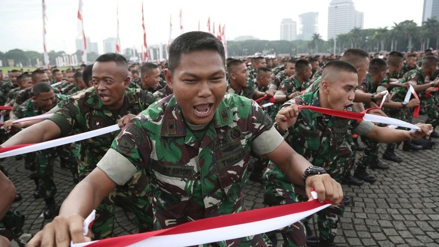 Indonesian soldiers perform national flag -colored headbands during a military-sponsored interfaith rally held ahead of the planned Dec. 2 Muslim protest against Jakarta Governor Basuki Tjahaja Purnama in Jakarta, Indonesia, Wednesday, Nov. 30, 2016. Thousands of Indonesians have joined interfaith rallies around the country organized by the military in an attempt to demonstrate national unity as religious and racial tensions divide the world's largest Muslim nation. (AP Photo/Achmad Ibrahim)