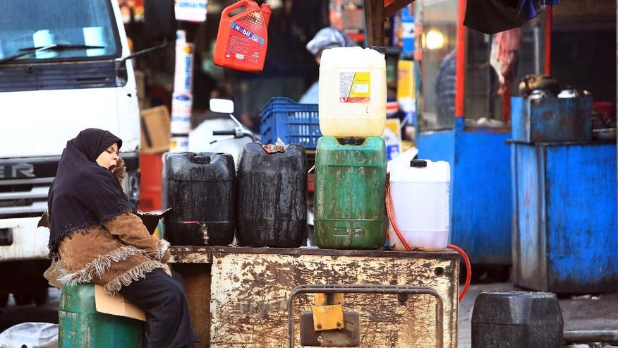 Fuel for sale on the sidewalk in Basra, 340 miles (550 kilometers) southeast of Baghdad, Iraq, Thursday, Dec. 1, 2016. War-weary Iraq hinges hopes on OPEC agreement to cut production to meet the massive needs of its costly, two-year-old war against the Islamic State extremist group, and to refresh its ailing, oil-reliant economy hammered by plummeted oil prices. (AP Photo/Nabil al-Jurani)