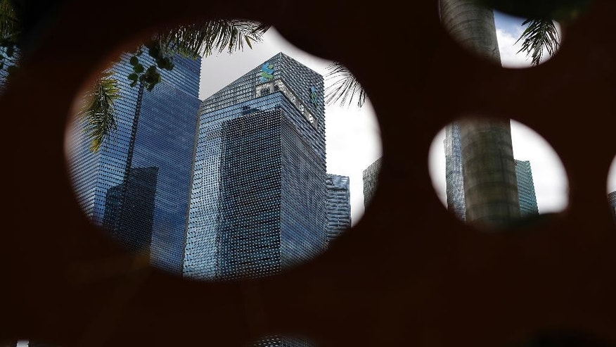 "The Standard Chartered building is seen framed by an art installation with holes in it, at the financial district of Singapore Friday, Dec. 2, 2016. Singapore regulators announced Friday fines amounting to over $5.3 million for two banks that were found to have breached money laundering rules in dealings with an indebted Malaysian state fund. The Monetary Authority of Singapore fined the local branch of Standard Chartered Bank, which is headquartered in London, 5.2 million Singapore dollars ($3.6 million) for ""significant lapses"" in customer due diligence measures and controls. (AP Photo/Wong Maye-E)"