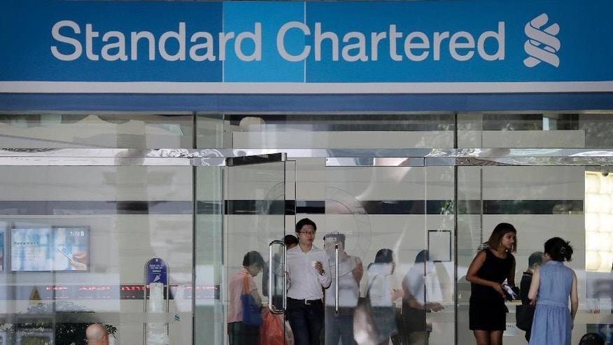 "Customers walk in and out of a Standard Chartered Bank branch in downtown Singapore Friday, Dec. 2, 2016. Singapore regulators announced Friday fines amounting to over $5.3 million for two banks that were found to have breached money laundering rules in dealings with an indebted Malaysian state fund. The Monetary Authority of Singapore fined the local branch of Standard Chartered Bank, which is headquartered in London, 5.2 million Singapore dollars ($3.6 million) for ""significant lapses"" in customer due diligence measures and controls. (AP Photo/Wong Maye-E)"