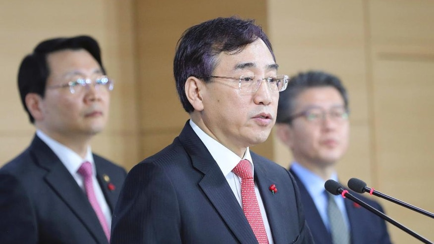 Lee Sukjoon, center, minister of the Office for Government Policy Coordination, answers a reporters' questions after announcing about sanctions on North Korea at the government complex in Seoul, South Korea, Friday, Dec. 2, 2016. South Korea announced Friday a set of largely symbolic, additional sanctions on North Korea for the nuclear and missile tests it conducted this year. (AP Photo/Lee Jin-man)