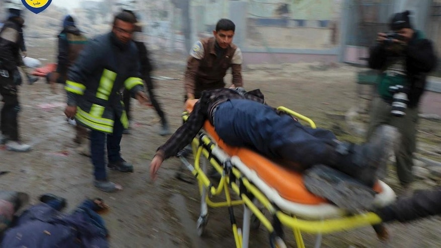 This photo provided by the Syrian Civil Defense White Helmets, which has been authenticated based on its contents and other AP reporting, shows Civil Defense workers carrying a victim on a stretcher after artillery fire struck the Jub al-Quba district in Aleppo, Syria, Wednesday, Nov. 30, 2016. Syrian activists say at least 21 people have been killed in an artillery barrage on a housing area for those displaced in rebel-held eastern Aleppo. (Syrian Civil Defense White Helmets via AP)