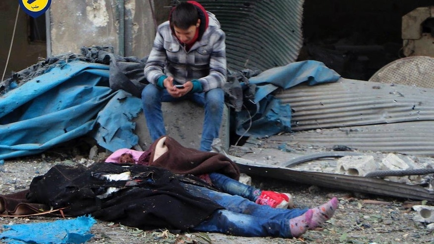 This photo provided by the Syrian Civil Defense White Helmets, which has been authenticated based on its contents and other AP reporting, shows a Syrian boy sittiing next to bodies after artillery fire struck the Jub al-Quba district in Aleppo, Syria, Wednesday, Nov. 30, 2016. Syrian activists say at least 21 people have been killed in an artillery barrage on a housing area for those displaced in rebel-held eastern Aleppo. (Syrian Civil Defense White Helmets via AP)
