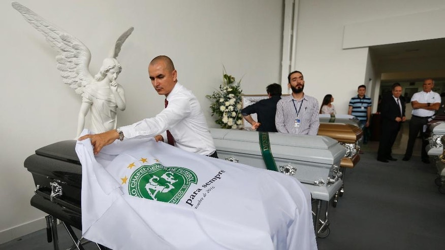 A funeral employee places a white sheet with a Chapecoense soccer team logo over a casket containing the remains of a team member, in Medellin, Colombia, Thursday, Dec. 1, 2016. Forensic authorities say they have managed to identify a majority of the victims of Monday's Colombian air tragedy and hope to finish their work on Thursday. (AP Photo/Fernando Vergara)