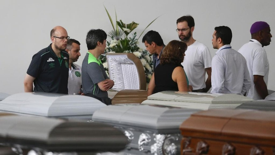 Members of Chapecoense soccer club's board of directors stand in the parking garage of the San Vicente funeral home where coffins containing the remains of the victims of the Colombian air tragedy have been placed, in Medellin, Colombia, Thursday, Dec. 1, 2016. Because of the large number of casualties, the funeral home had to place the coffins in its parking garage. Forensic authorities say they have managed to identify a majority of the victims of Monday's crash and hope to finish their work on Thursday.  (AP Photo/Fernando Vergara)