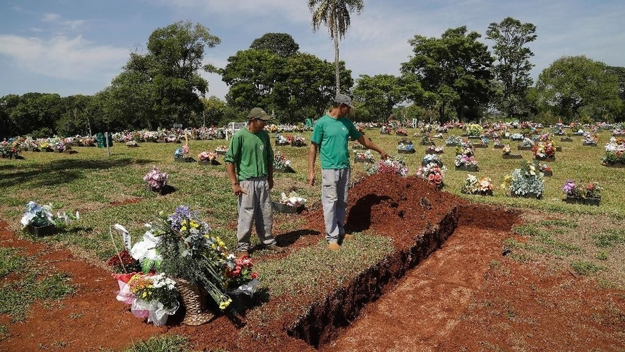 Cemetery workers prepare burial sites in Chapeco, Brazil, Friday, Dec. 2, 2016, as Colombia begins repatriating the dead from a chartered plane crash. The bodies of the Brazilian victims will be repatriated later Friday on three flights to Chapeco, the hometown of the Chapecoense Brazilian soccer team. Members of the team and a group of journalists who perished on the flight were headed to the Copa Sudamericana finals when the plane ran out of fuel, crashing into the Andes outside Medellin. (AP Photo/Andre Penner)