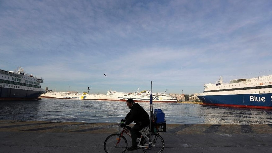 A man rides his bicycle past docked ferries at the port of Piraeus, near Athens, Friday, Dec. 2, 2016. Ferries across Greece are to remain tied up in port for two days as seamen walk off the job to protest proposed tax hikes. (AP Photo/Thanassis Stavrakis)